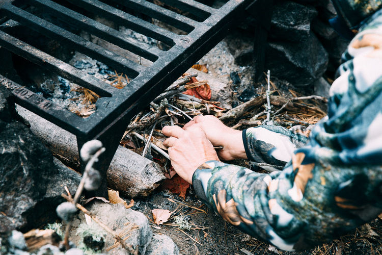 Cropped Image Of Person Igniting Campfire Under Metal Grate