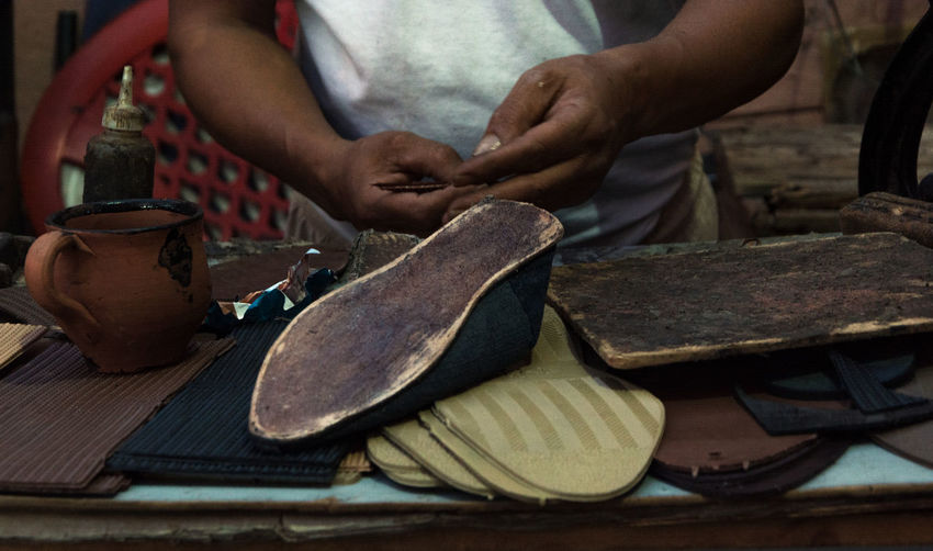 Midsection of man working on shoe in workshop