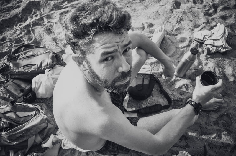High angle portrait of shirtless man holding drink glass while sitting at beach