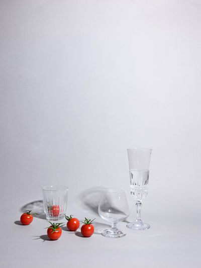 Fruits in glass on table against white background