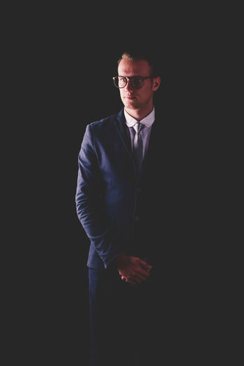 Black Background Business Business Person Businessman Copy Space Dark Eyeglasses  Formalwear Front View Glasses Indoors  Males  Men Menswear One Person Serious Standing Studio Shot Three Quarter Length Well-dressed Young Adult Young Men