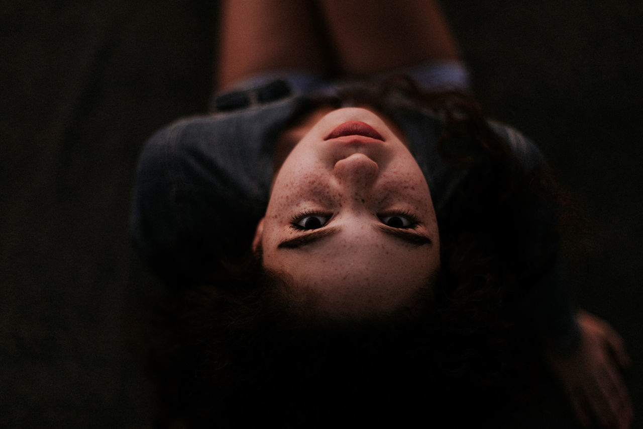 Close-up high angle view of young woman resting in darkroom