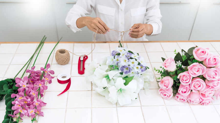 Midsection of woman making bouquet in flower shop