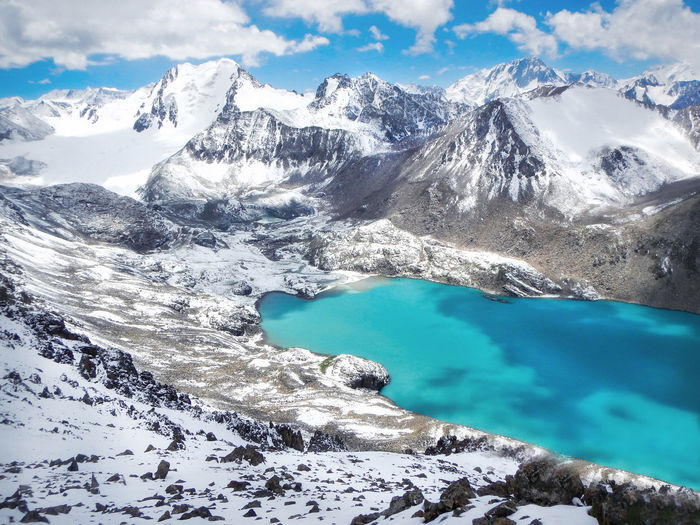 Scenic View Of Lake Amidst Snowcapped Mountains During Winter