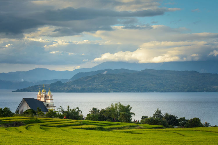 The church building that stands on the edge of the edge of Lake-Toba (danau toba) in North Sumatra, Indonesia in Balige area. Architecture Balige Beauty In Nature Building Exterior Built Structure Church Church Architecture Church Buildings Church Tower Churches Churchyard Cloud - Sky Danau Toba Gereja Grass Green Color INDONESIA Indonesia_photography Landscape Mountain Mountain Range No People Outdoors Sky SUMATERA UTARA