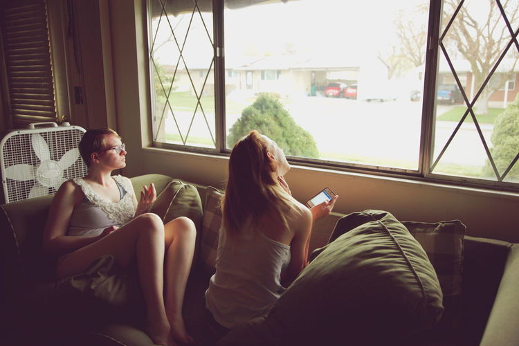 Domestic Life Friends Hanging Out Home Interior House Indoors  Living Room Looking Out Of The Window Natural Light Person Relaxation Sisters Sitting Sofa Together Window Young Adult Young Women
