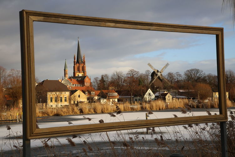 Traditional windmill and tower seen through frame during winter