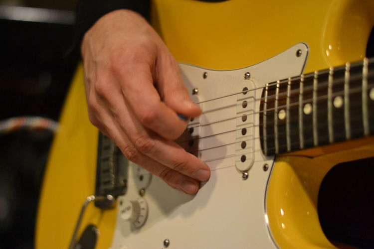 Cropped hand of guitarist playing yellow electric guitar