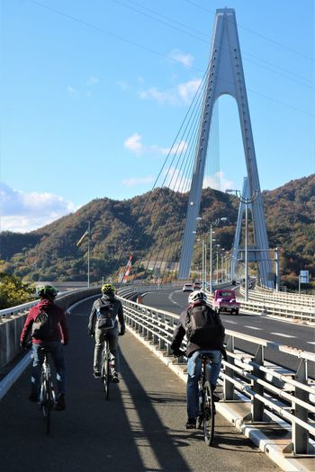 People riding bicycle on cable stayed bridge