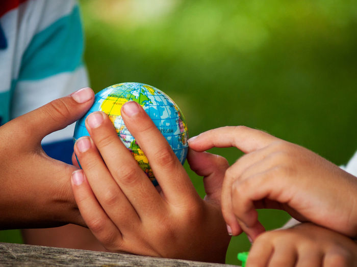 Midsection of boy holding globe on table