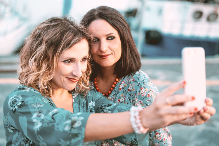 Women Two People Portrait Females Adult Smiling Communication Emotion Young Women Mid Adult Women Togetherness Happiness Selfie Mobile Phone Positive Emotion Casual Clothing Young Adult Mid Adult Headshot Wireless Technology Taking Selfies Teal And Orange Filtered