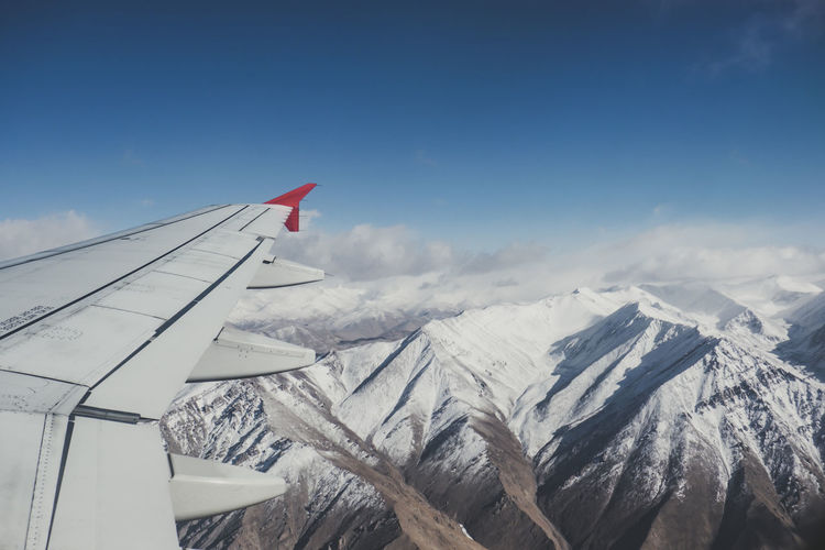Airplane flying over snowcapped mountains against sky