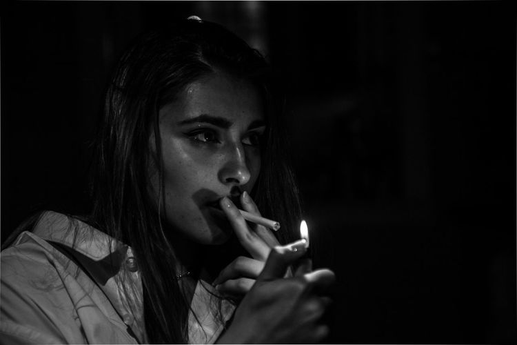 Close-up of woman igniting cigarette against black background