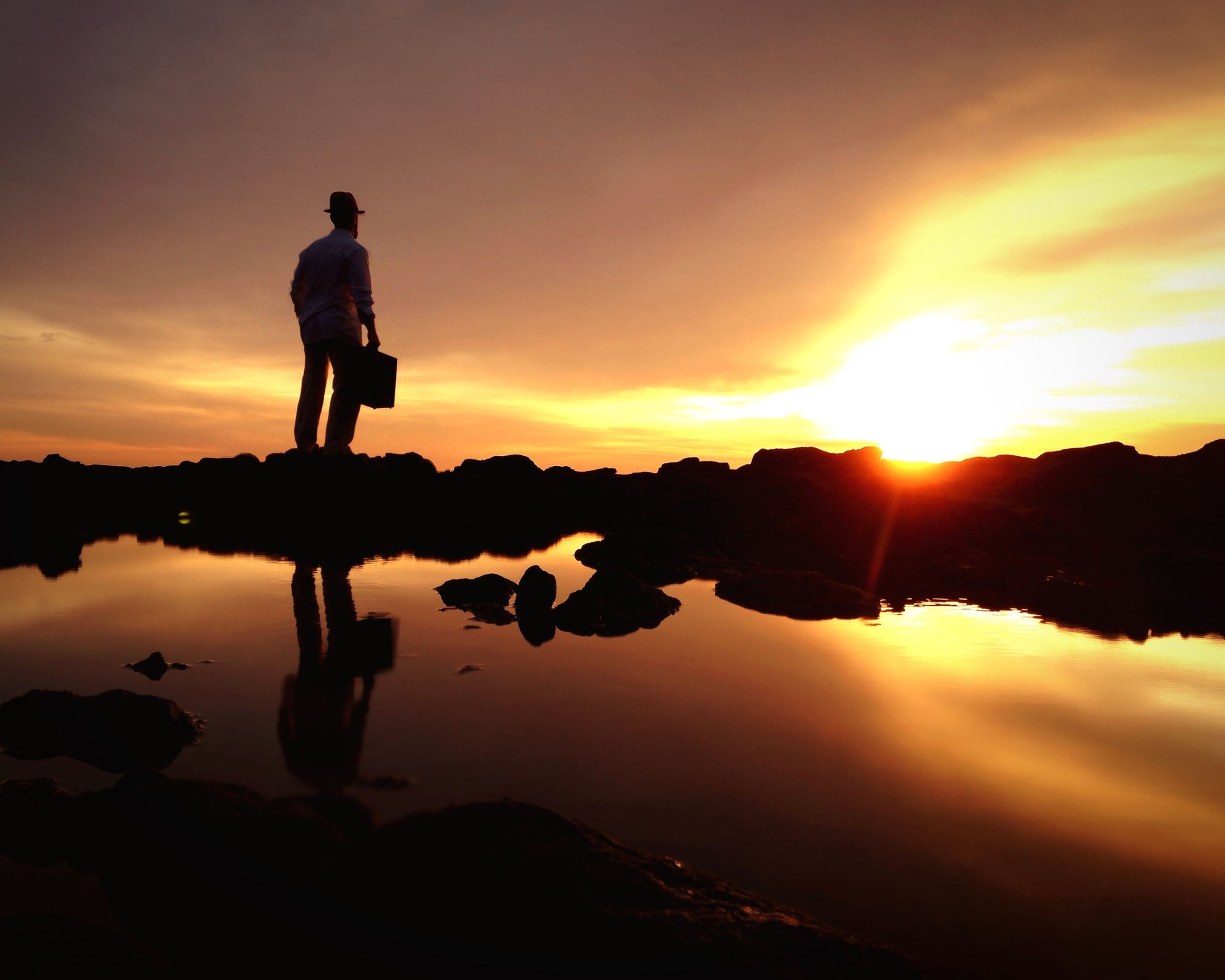 sunset, silhouette, sky, water, leisure activity, lifestyles, sun, scenics, beauty in nature, tranquil scene, men, orange color, tranquility, reflection, mountain, standing, full length, nature