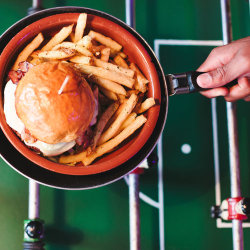 Close-up of hand holding burger and french fries in frying pan over foosball table