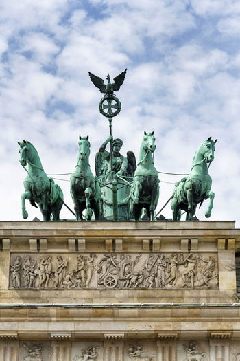 Quadriga on Brandenburg Gate, dramatic cloudy sky background, Berlin, Germany Brandenburger Tor Brandenburg Gate Quadriga Berlin Germany Dramatic Cloudy Sky Blue Background Landmark Statue Symbol National Monument Pariser Platz Neoclassical Architecture City Travel Europe Famous Capital Urban Tourism Old History Column View Culture Sightseeing Historic Wall Place Cityscape Scene Street Horse Center Sculpture Destination Square Exterior Copy Space Vertical
