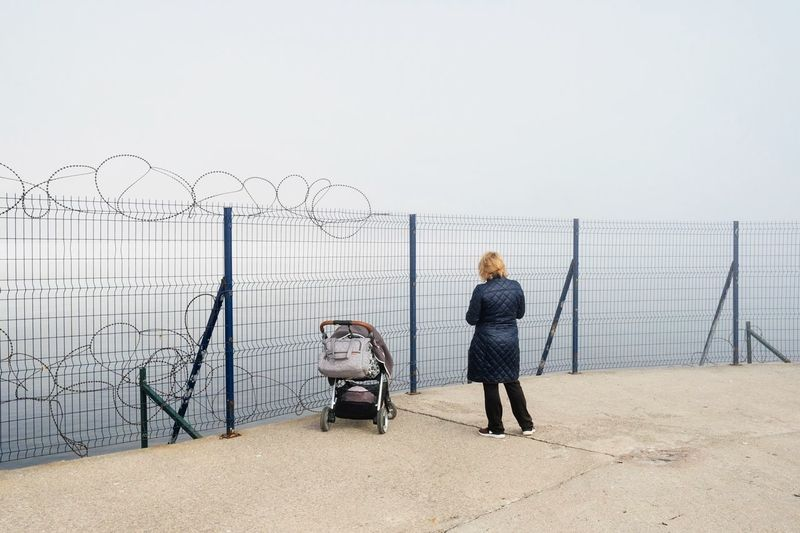 Woman With Baby Stroller Standing By Fence Against Sky