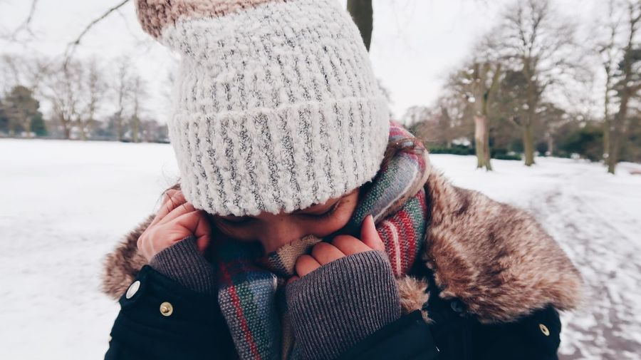 Close-up of woman covering face while standing outdoors during winter