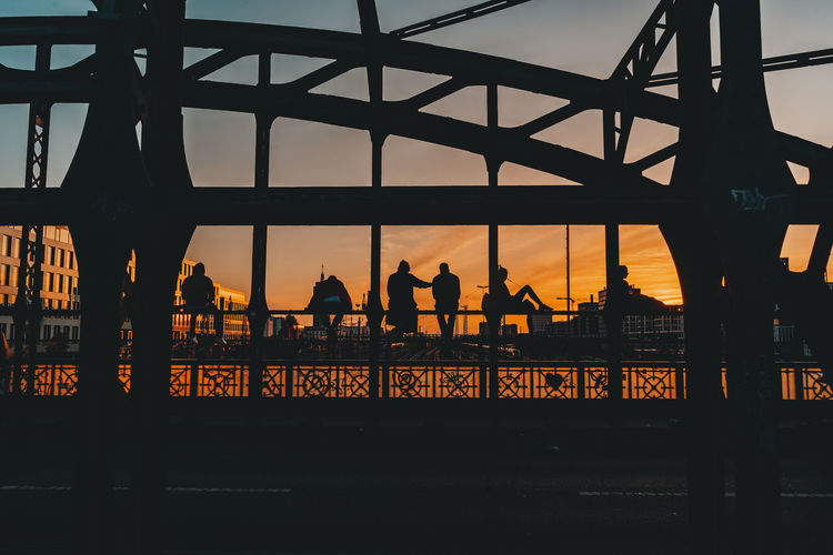 Silhouette people on bridge in city against sky during sunset