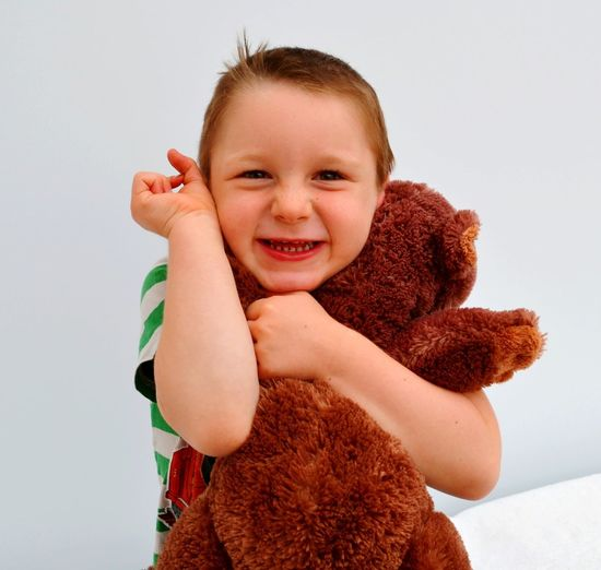 Portrait of cute smiling boy holding stuffed toy against white wall at home