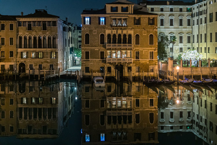Reflection of residential buildings on the grand canal in venice at night.
