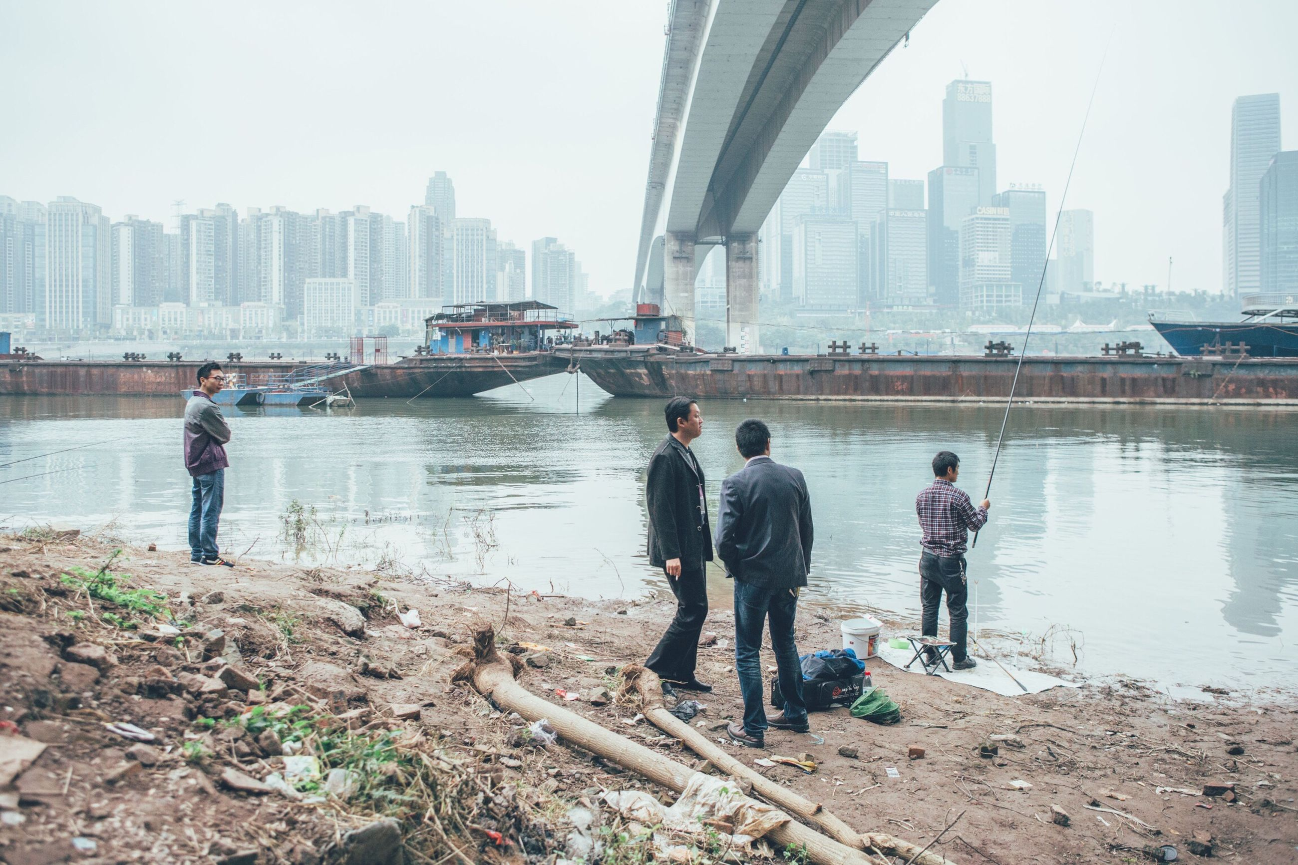 building exterior, architecture, real people, built structure, leisure activity, lifestyles, river, city, water, skyscraper, togetherness, full length, bridge - man made structure, day, men, urban skyline, sky, outdoors, nature, cityscape, people