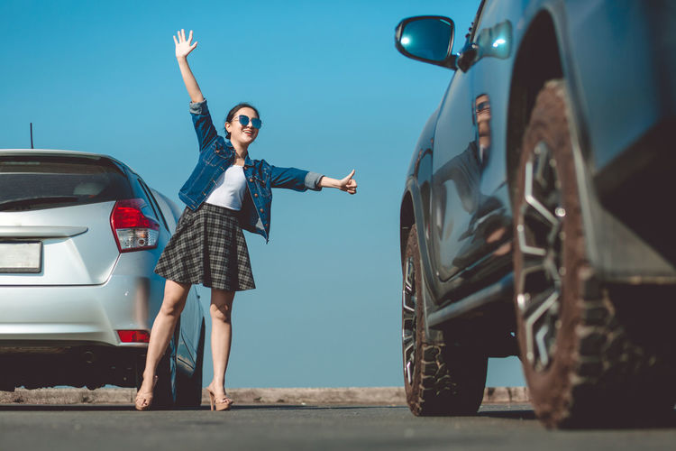 Full length of woman standing by car against sky