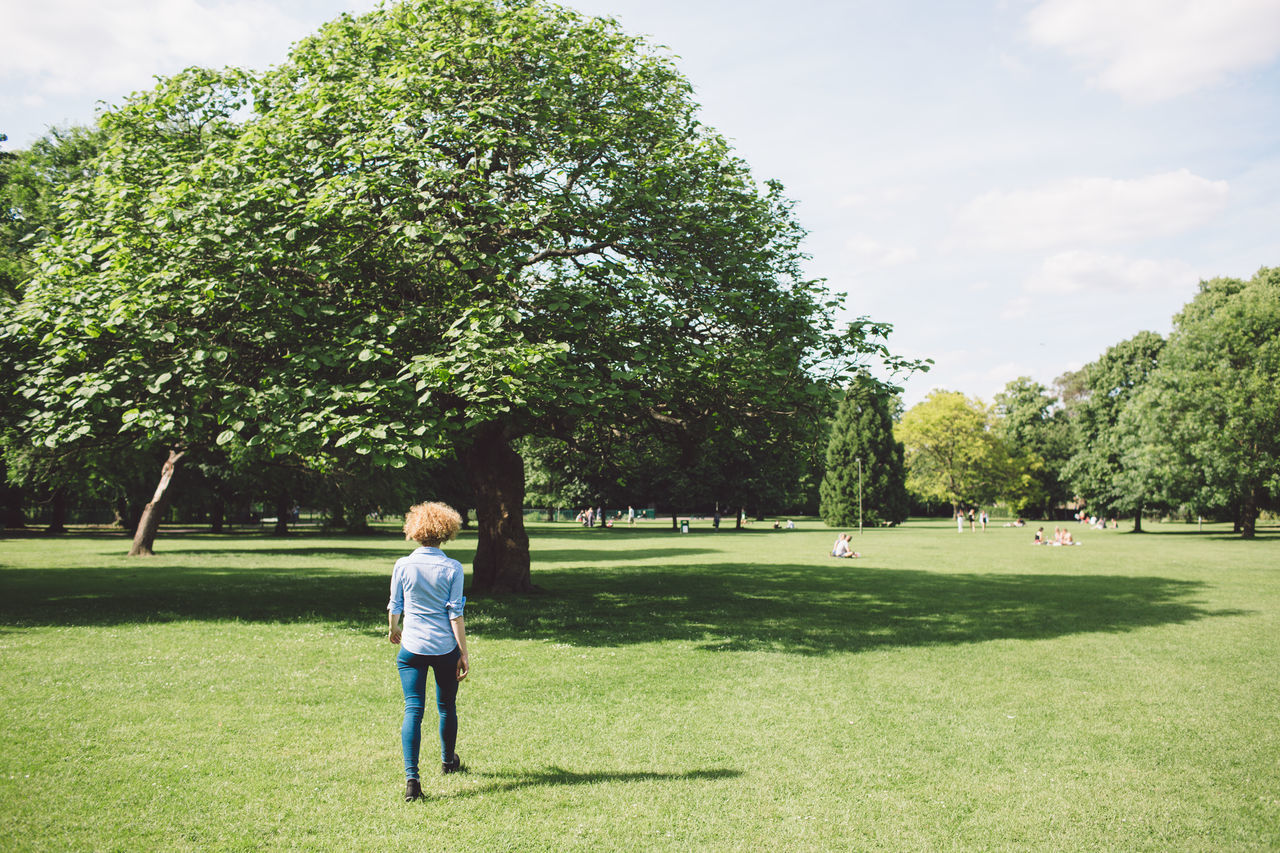 Rear View Of Woman Walking On Field At Park During Sunny Day