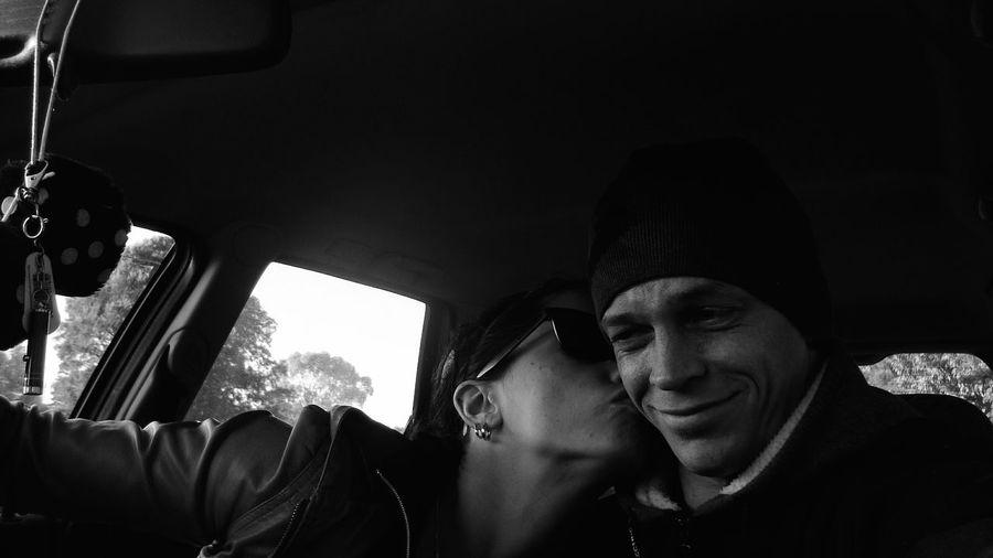Woman kissing boyfriend on cheek in car
