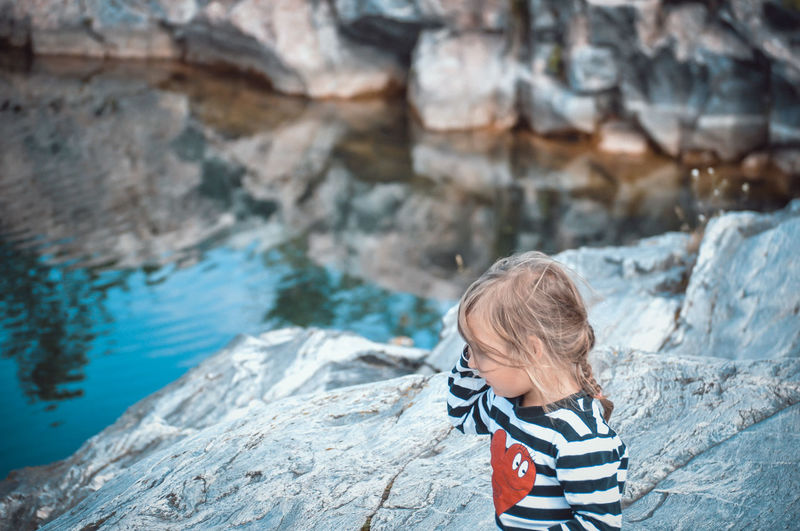 Rear view of boy on rock at shore