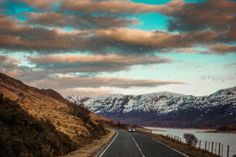 Road by mountains against sky seen through car windshield