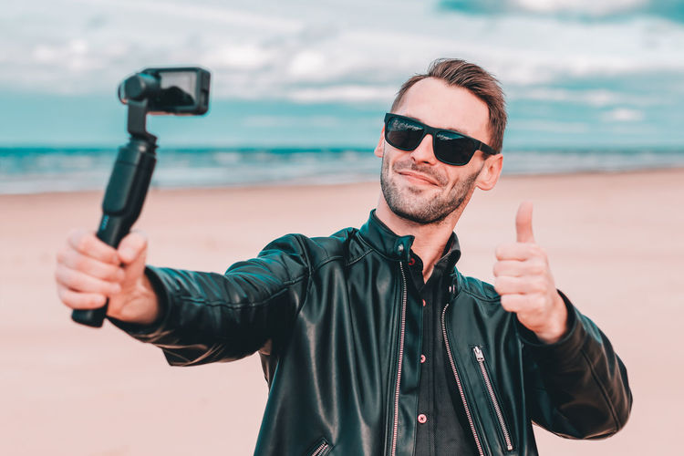 Smiling young man wearing sunglasses filming with video camera at beach