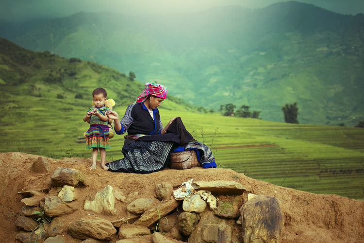 Woman with daughter sewing fabric on rock