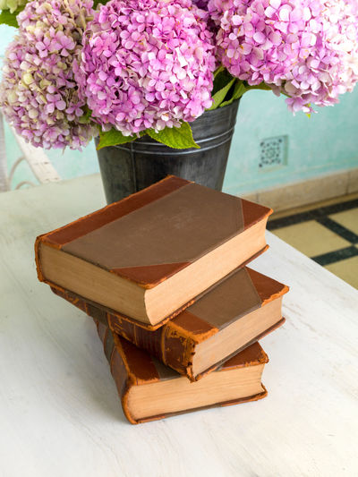 Old books resting on white table, decorated with flowers