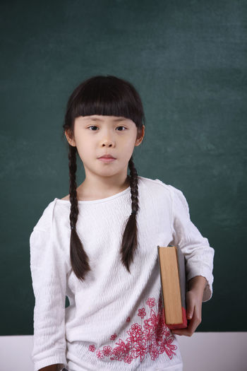 Portrait Of Girl Holding Book While Standing By Blackboard