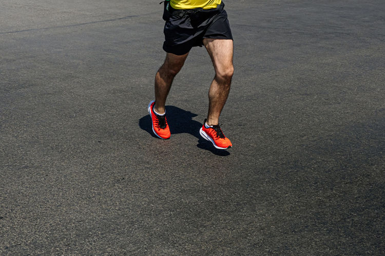 Low section of man running on street