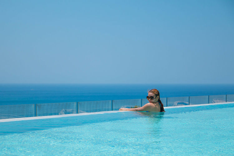 Beautiful woman in infinity pool by sea against clear blue sky