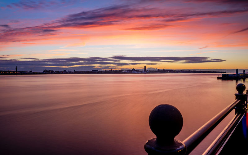 The water of the River Mersey is silky smooth as the evening sun has set down and painted the sky crimson. Blue Hour Liverpool Waterfront Liverpool, England Architecture Buildings City Merseyside No People Outdoors Reflections In The Water River Sky Summer Sunset Water Waterfront
