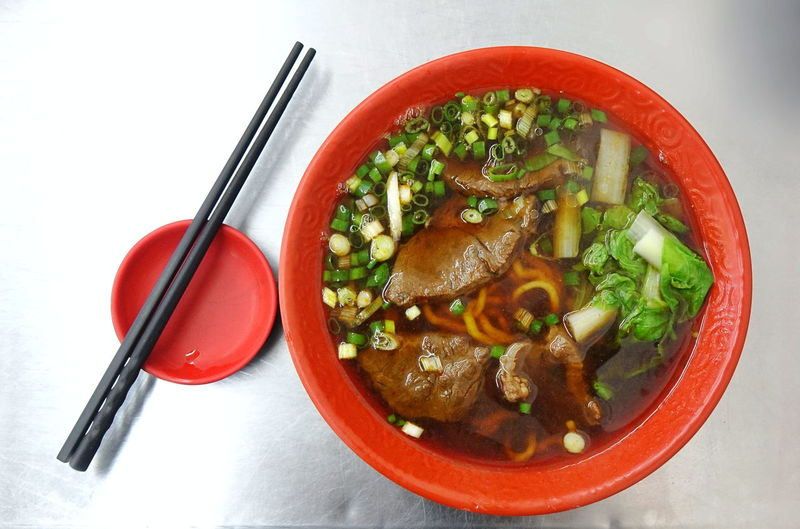 A bowl of beef noodles with chives and vegetables, a popular Chinese dish in Taiwan. Beef Noodles Braised Beef Noodle Soup Chinese Food Taiwan Food Broth Chives Chopsticks Food High Angle View Leeks Meat Plate Restaurant Soup Bowl