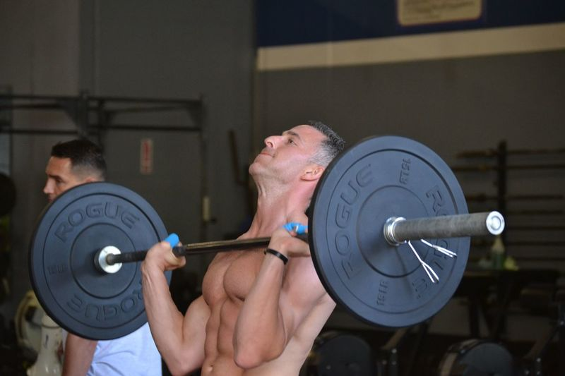 Mature Man Holding Barbell At Gym