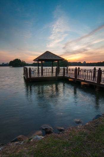 Jetty in lake against sky during sunset