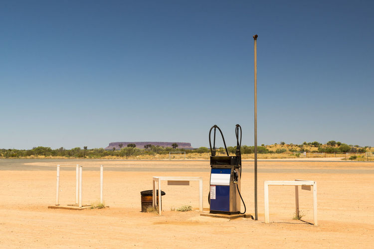 Fuel pump at desert against clear blue sky