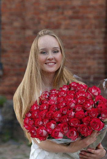 Portrait of smiling young woman holding red flower