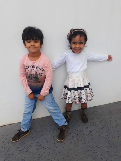 Full length portrait of boy with sister standing against wall