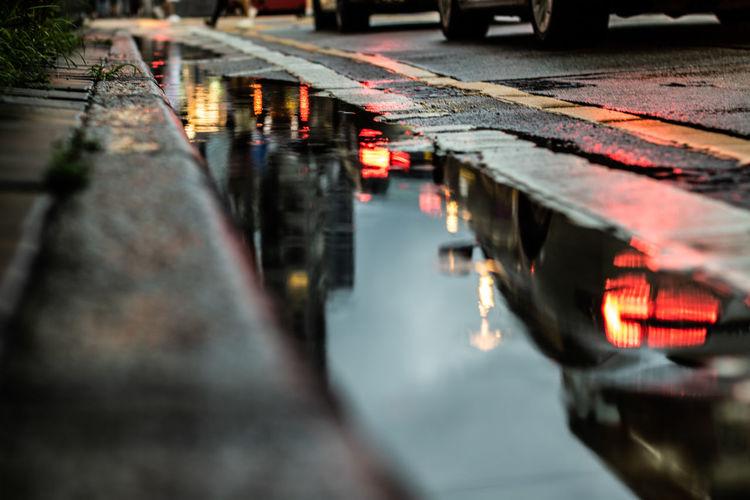 Reflection of illuminated bridge on canal in city