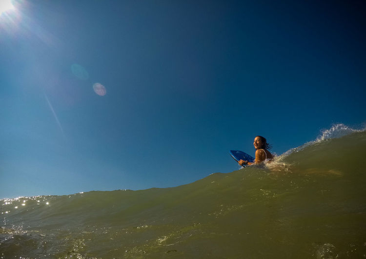 Low Angle View Of Girl Surfing In Sea Against Clear Blue Sky