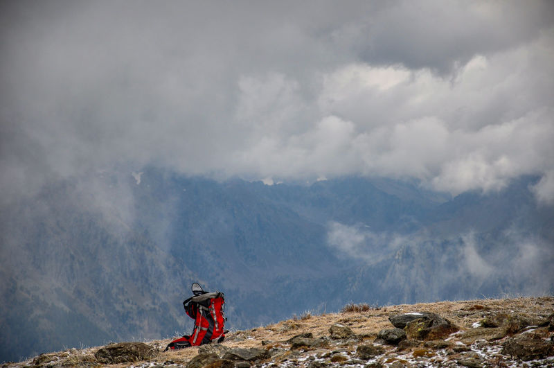 Backpack on mountain peak against cloudy sky