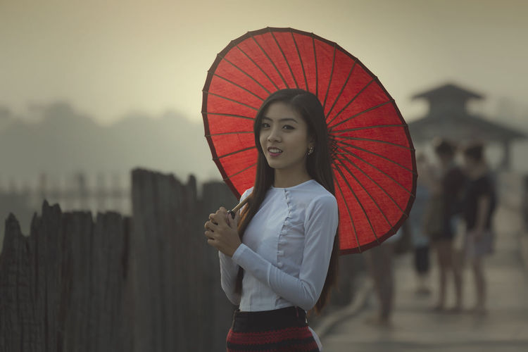 Portrait of young woman with umbrella standing on pier against sky