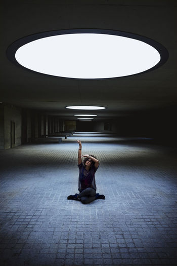 Full length of woman sitting in illuminated tunnel