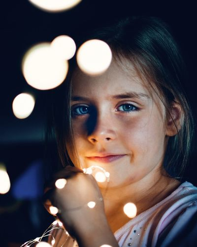 Portrait of girl with illuminated string light in dark at night